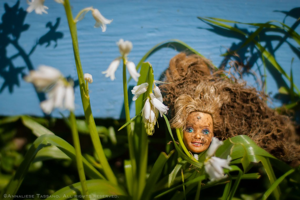 A dirty Barbie doll head, recently dug up from the garden is displayed in front of a bright blue house, nestled in greens and white flowers.