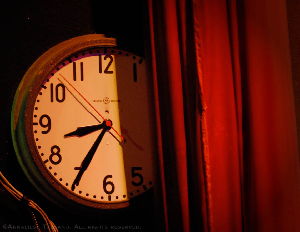 A General Electric analogue clock face side stage and partly obscured by a red curtain reads 8:35 at Portland, Oregon's Alddin Theater.