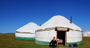 Me sitting in front of a yurt in Kyrgyzstan and my solar panel charging my mobile phone
