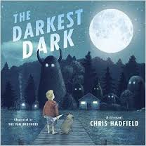 Boy stands outside in the dark, with monstrous shapes around him, but he stares at full moon above him.