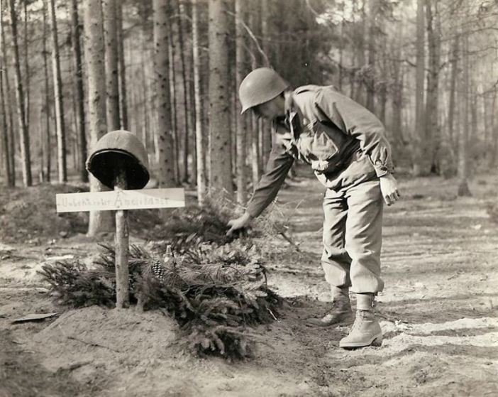 U.S. Soldier examines the grave of an unknown U.S. soldier, who was buried by the enemy before retreating. The first American soldier that noticed the grave, decorated it with mortar shells and ferns.