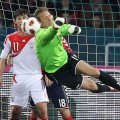 Armenian goalkeeper Roman Berezovsky jumps for the ball.