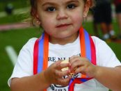 Two-year-old Angele Chalian fingers a medal after finishing the kiddie race. She's the daughter of Hrag & Taline (Hagopian) Chalian of New Jersey.