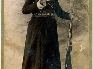 Image of the postcard found in the wall of an Armenian home in Ayntap: Heghine, the widow of Kevork Chavoush, with Mauser handgun in her right hand and a shortened-barrel (or stage prop) Mosin rifle in her left