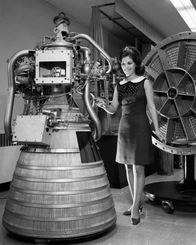 Miss NASA 1968/1969 with RL-10 engine display. Rocket Operations Building, Rob Control Room.