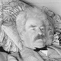 Mark Twain reclines on a sofa with a book. --- Image by © CORBIS