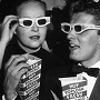 November 1952:  EXCLUSIVE American actor Keefe Brasselle and his wife Norma, wearing 3-D glasses and holding boxes of hot buttered popcorn, sit in the theater at the premiere of director Arch Oboler's film, 'Bwana Devil,' Hollywood, California. The film was the first commercial 3-D feature. In the background American actor Charles Coburn is visible.  (Photo by M. Garrett/Murray Garrett/Getty Images)