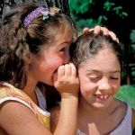 ca. 1999, France --- Girl whispering into sister's ear --- Image by © G. Bowater/Corbis