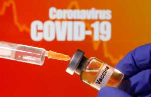 "A small bottle labeled with a ""Vaccine"" sticker is held near a medical syringe in front of displayed ""Coronavirus COVID-19"" words in this illustration taken April 10, 2020. REUTERS/Dado Ruvic/Illustration"