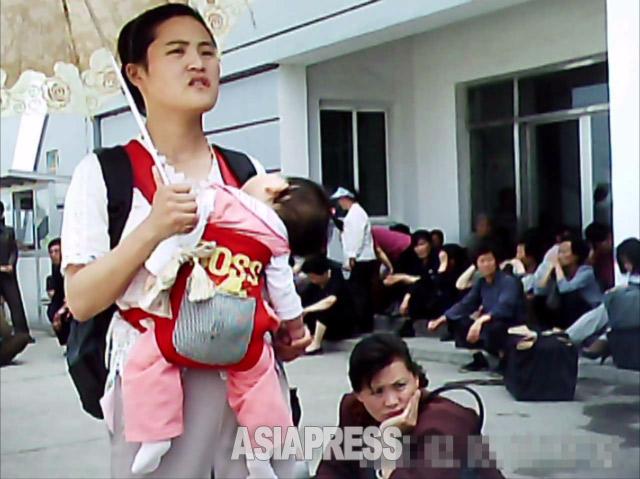 「だっこ紐」で子供を抱く女性。5年ほど前までは「ねんねこ」でおぶるのが一般的だった。中国製だという。輸入品を通じて外国の文化や情報が国内に流入する。2011年6月平壌市中区でク・グァンホ撮影(アジアプレス)