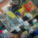 시장에서 술을 팔고 있는 여성. 매대에 '알콜 93%, 인삼심보술'이라는 상표가 붙은 병들이 놓여있다