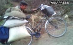 자전거로 힘겹게 식량을 나르는 '되거리' 상인. 2010년 10월 평안남도에서. 촬영 김동철 (아시아프레스)