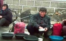 철도 역 앞에서 대야에 든 세면용 물을 파는 여성들. 공공 시설에서도 단수가 상시화되고 있다. 2013년 3월 평안남도 평성시에서. 촬영 '민들레'(아시아프레스)