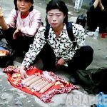 The reporters for the congress should report only about 'the developing Pyongyang.' Ordinary people in Pyongyang earn a living through a business. A woman in the photo is selling Chinese made sausages. Taken by Koo Gwang-ho at Moranbong District on June 2011. (ASIA PRESS)