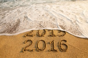 New year 2016 and old year 2015 written on sandy beach with waves