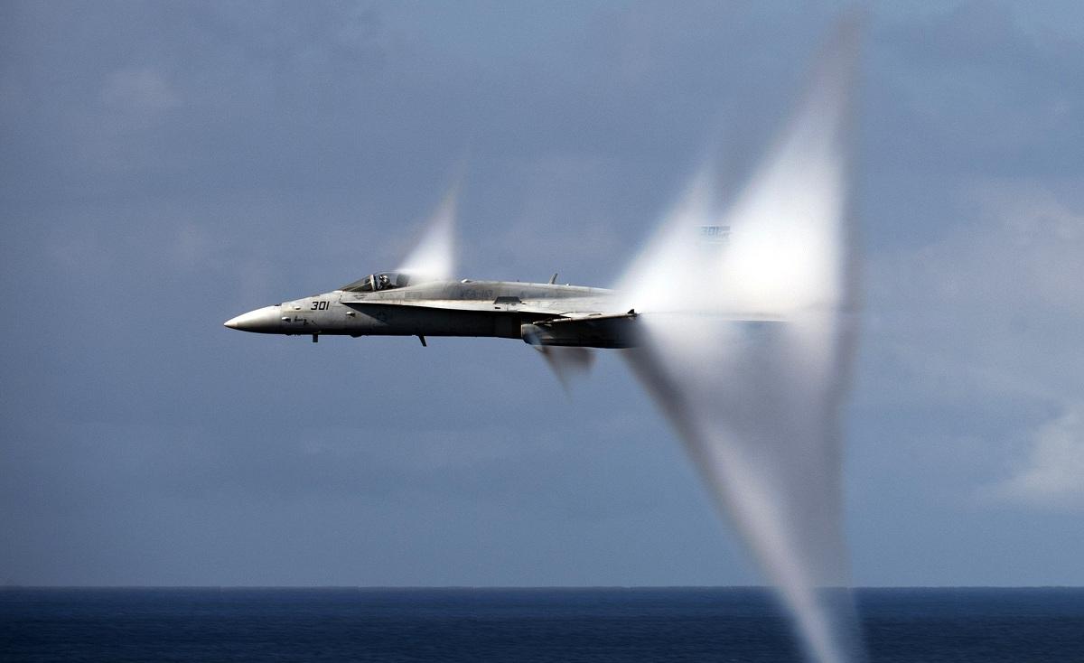 """F/A-18E no exato momento em que ultrapassa a barreira do som. A imagem permite ver o """"cone transônico"""", a região onde ocorre um salto abrupto de pressão e a umidade do ar se condensa. Imagem: fonte desconhecida."""