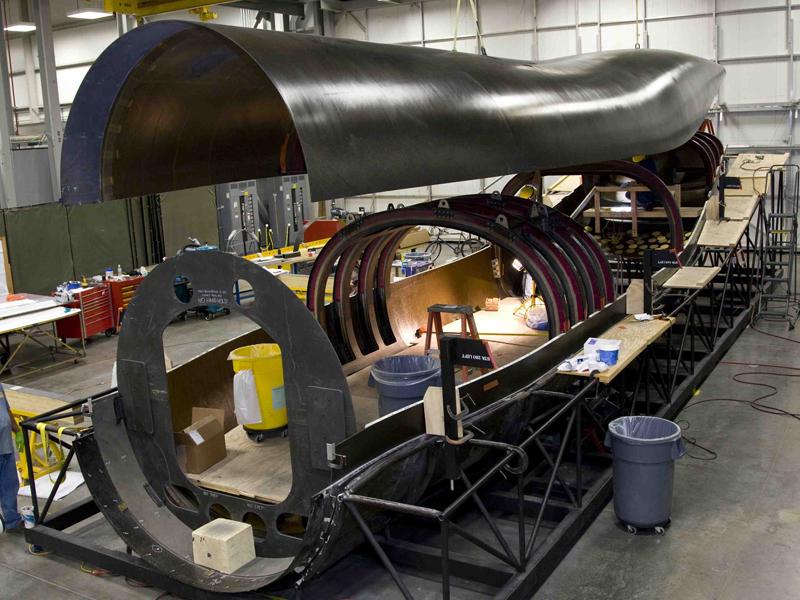 Montagem da fuselagem do cargueiro X-55A. Com 18 m de comprimento e feita com compósitos de carbono/epoxy, reduziu-se em 10 vezes a quantidade de partes e em mais de 100 vezes a quantidade de fixadores. Imagem: CompositesWorld (www.compositesworld.com).