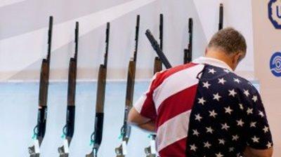 Man in flag shirts examines guns (NRA)