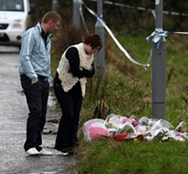 An upset couple arrive at the murder scene to lay flowers where Stuart Walker was brutally murdered