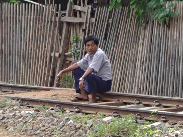 Local man sitting having a cigarette at the train station (Myanmar, 2016).