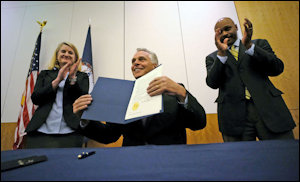 Governor Terry McAuliffe displays his CO2 emissions executive order. Photo credit: Richmond Times-Dispatch