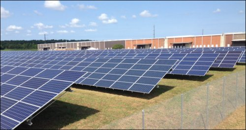 Solar panels at Dominion's Philip Morris USA site with warehouses in the background.