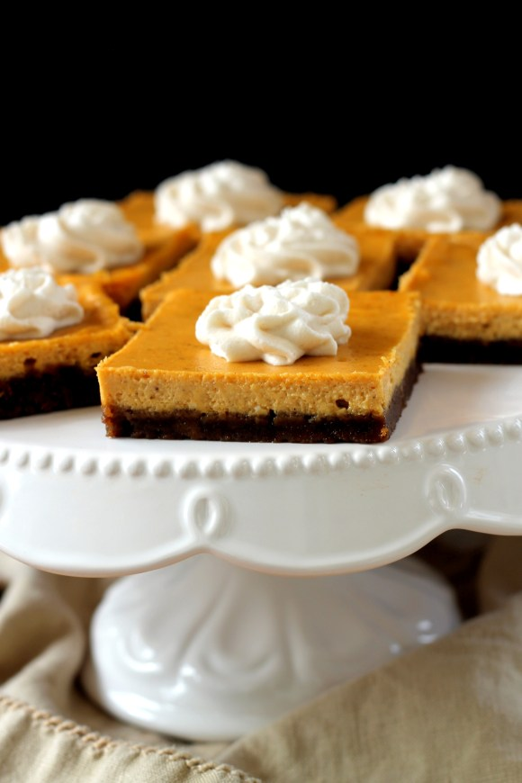 These Gingersnap Pumpkin Cheesecake Bars have a crunchy gingersnap cookie crust topped with a luscious, smooth pumpkin cheesecake filling. You'll love these spiced bars!