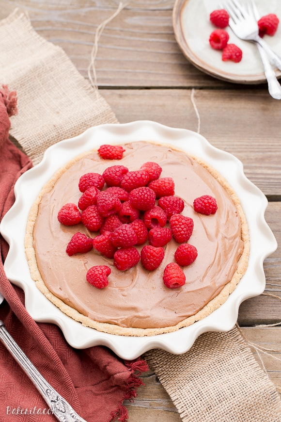 This Paleo Fresh Raspberry French Silk Pie has an almond flour crust filled with a super creamy chocolate pie filling. Fresh raspberries add brightness to this rich dessert.