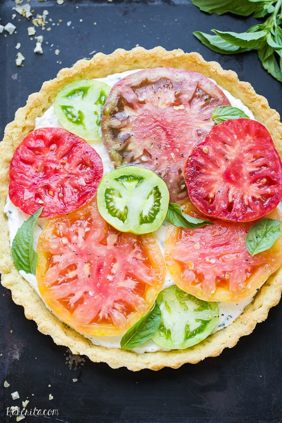 This Ricotta Heirloom Tomato Tart has a gluten-free cornmeal crust and basil ricotta filling, topped with beautiful heirloom tomatoes! This simple tart makes a wonderful appetizer, lunch, or dinner.