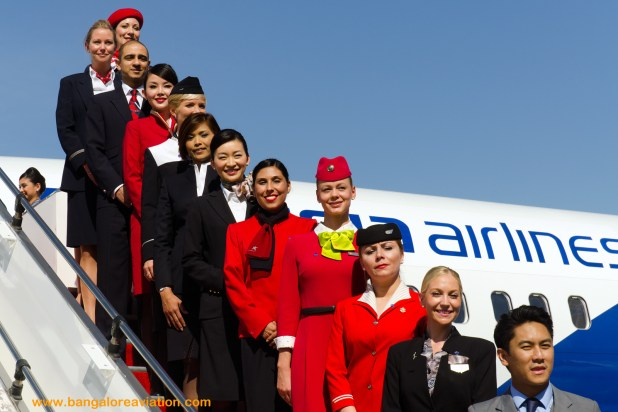 """Uniformed cabin crew representatives from each of the oneworld member airlines standing top to bottom of the stairs in alphabetical order. AirBerlin, American Airlines, Cathay Pacific, Finnair, Iberia, Japan Airlines, LAN Chile, QANTAS, Royal Jordanian, S7 Russian Airlines, and Malaysia Airlines. The Master or rather mistress of ceremonies kept referring to the crew as """"girls"""" requesting them to line up, forgetting that British Airways was represented by Mr. Dave."""