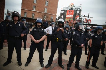 BALTIMORE, MD - APRIL 25: Police in riot gear stand guard at Camden Yard during a march in honor of Freddie Gray on April 25, 2015 in Baltimore, Maryland. Gray, 25, was arrested for possessing a switch blade knife outside the Gilmor Homes housing project on Baltimore's west side on April 12. According to his attorney, Gray died a week later in the hospital from a severe spinal cord injury he received while in police custody. (Photo by Alex Wong/Getty Images) ORG XMIT: 550492749 ORIG FILE ID: 471170832