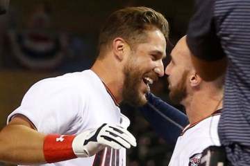 Minnesota Twins' Trevor Plouffe, left, is congratulated by Shane Robinson after his walk-off home run off Cleveland Indians relief pitcher Bryan Shaw in the 11th inning of a baseball game, Friday, April 17, 2015, in Minneapolis. The Twins won 3-2. (AP Photo/Jim Mone)