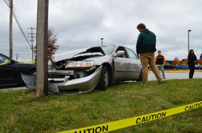 Investigator Brayden Parker prepares to examine the contents of the damaged vehicle and the surrounding crime scene.