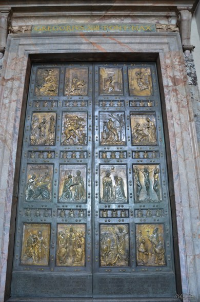 """The northernmost door is the """"Holy Door"""" which, by tradition, is walled-up with bricks, and opened only for holy years such as the Jubilee year by the Pope. The present door is bronze and was designed by Vico Consorti in 1950. Above it are inscriptions commemorating the opening of the door: PAVLVS V PONT MAX ANNO XIII and GREGORIVS XIII PONT MAX. Recent commemorative plaques read: PAVLVS VI PONT MAX HVIVS PATRIARCALIS VATICANAE BASILICAE PORTAM SANCTAM APERVIT ET CLAVSIT ANNO IVBILAEI MCMLXXV Paul VI, Pontifex Maximus, opened and closed the holy door of this patriarchal Vatican basilica in the jubilee year of 1975. IOANNES PAVLVS II P.M. PORTAM SANCTAM ANNO IVBILAEI MCMLXXVI A PAVLO PP VI RESERVATAM ET CLAVSAM APERVIT ET CLAVSIT ANNO IVB HVMANE REDEMP MCMLXXXIII – MCMLXXXIV John Paul II, Pontifex Maximus, opened and closed again the holy door closed and set apart by Paul VI in 1976 in the jubilee year of human redemption 1983-4. IOANNES PAVLVS II P.M. ITERVM PORTAM SANCTAM APERVIT ET CLAVSIT ANNO MAGNI IVBILAEI AB INCARNATIONE DOMINI MM-MMI John Paul II, Pontifex Maximus, again opened and closed the holy door in the year of the great jubilee, from the incarnation of the Lord 2000–2001."""