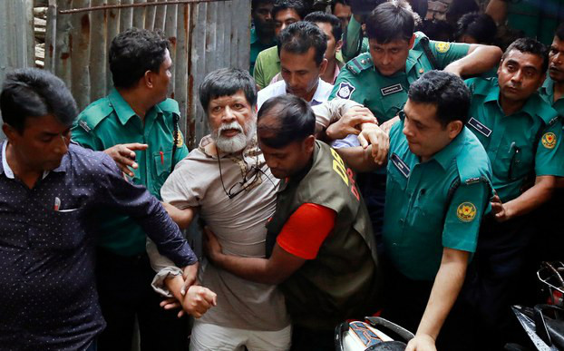 Officers move photographer Shahidul Alam to a Dhaka court where a judge allowed a seven-day remand for police to question him regarding statements about the student protests, Aug. 6, 2018.