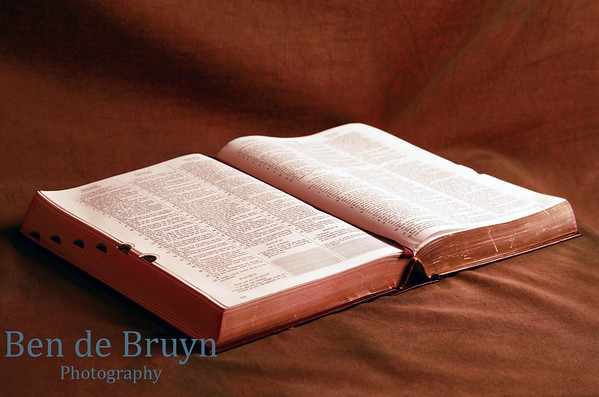 The holy Bible open against a brown earth colored background containing the salvation story via Jesus Christ