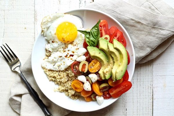 This quinoa breakfast bowl is and easy and healthy gluten free recipe packed with protein and nutrition from the sweet cherry tomatoes and olives, eggs, and quinoa