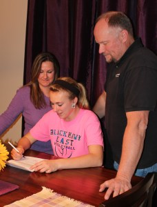 Lindsey signs letter of intent as her parents look on.
