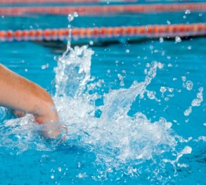 Arms of swimmer diving into pool