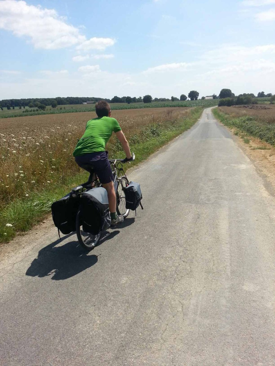 Photograph of man cycling down a country lane in Brittany, France.