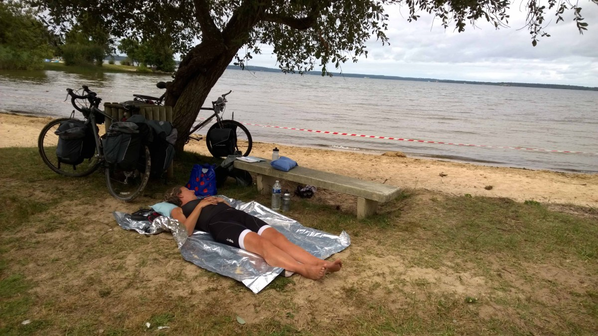 Photograph of Sarah lying asleep on the ground next to a lake and bicycles.