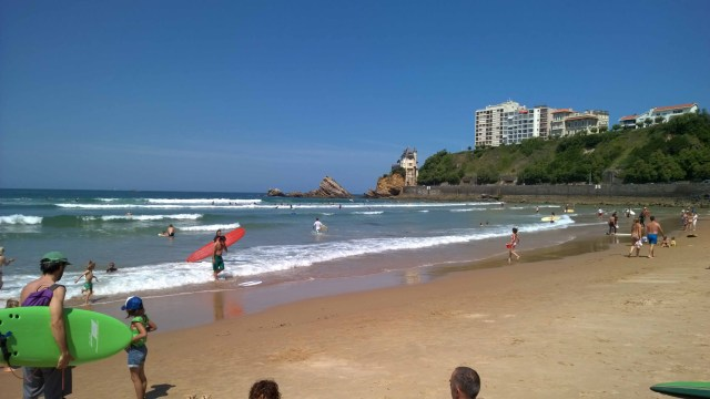 Photograph of Biarritz surf beach on a sunny day with swimmers and surfers in the sea.