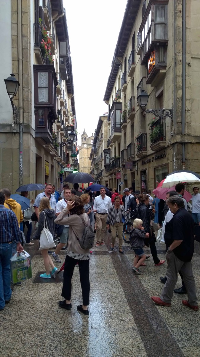 Photograph of rainy, crowded street in San Sebastian Old Town, Basque Country, Spain.