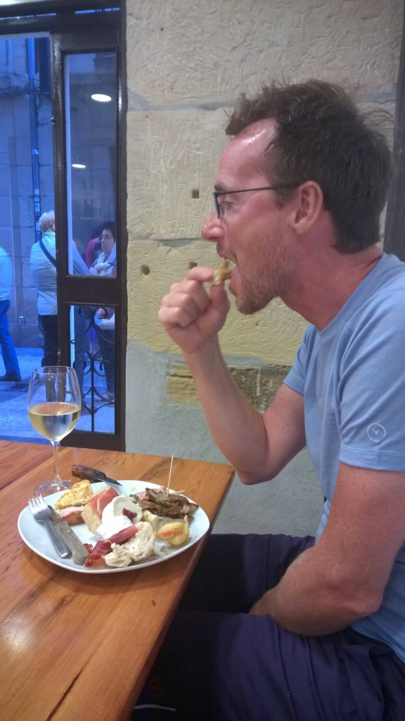 Photograph of Keith in a bar in San Sebastian, Basque Country, Spain, eating pinxos and drinking copa vino blanco.