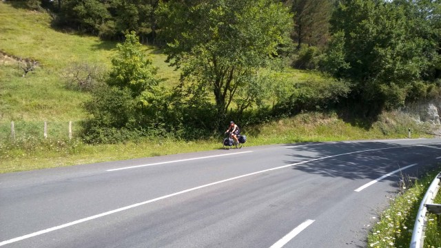 Photograph of Sarah cycling up a deserted country road in Basque Country, Spain.