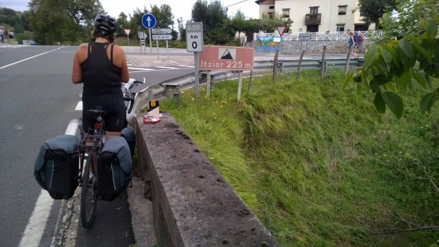 Photograph of Sarah on her bicycle from behind stopped at a junction in Basque Country, Spain.