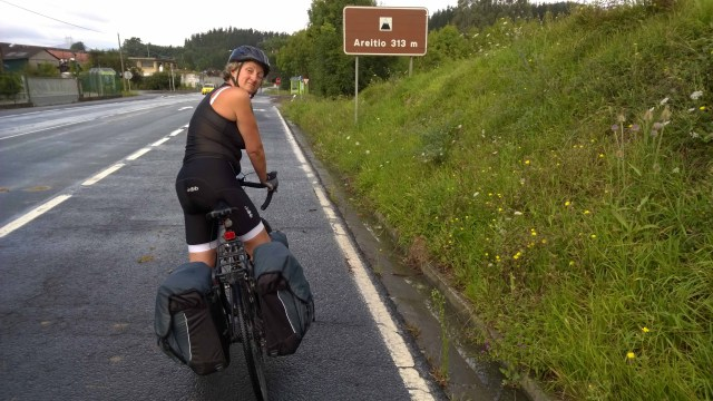 Photograph of Sarah cycling up a hill with a sign which says 'Aretitio 313m'.