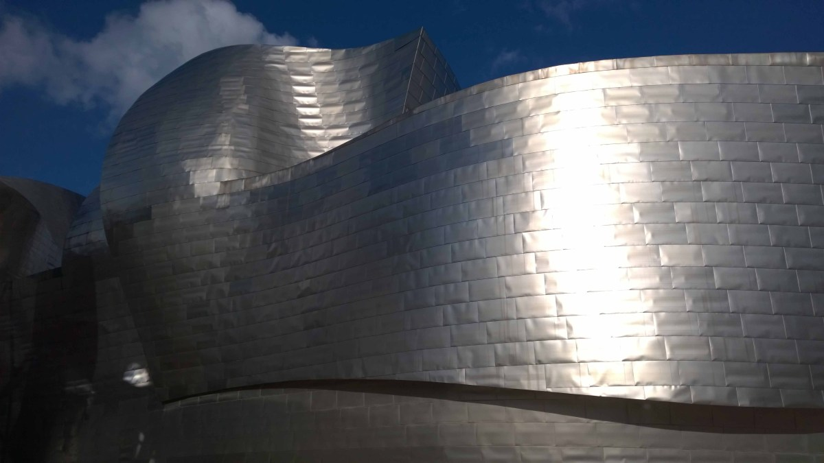 Photograph of the silver, curved walls of the Guggenheim, Bilbao.