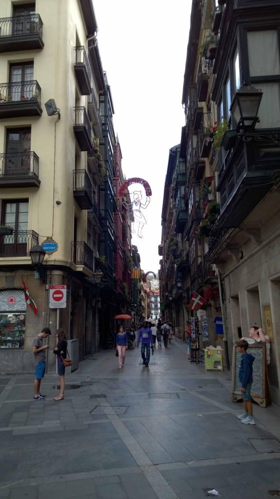 Photograph of a rainy street and people in Bilbao Old Town.