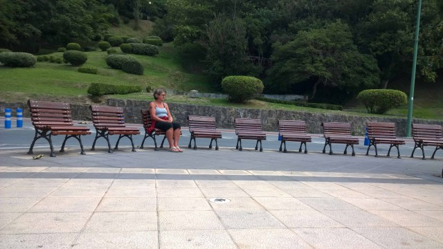 Photograph of Sarah sitting alone on a line of benches only big enough for one person.